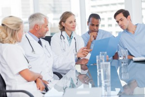 5 doctors sat at table looking at folder